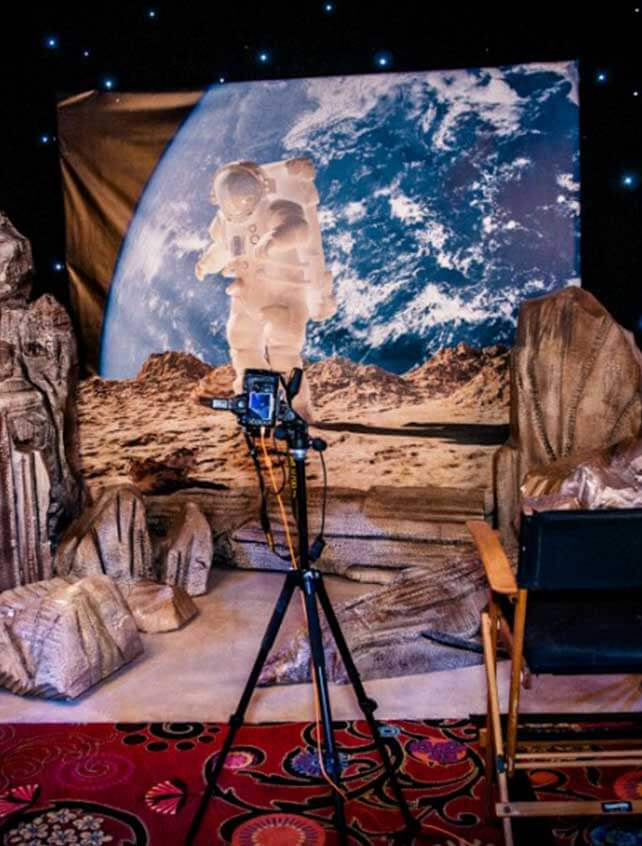 A set containing a backdrop printed with an astronaut in space sis behind a molded rock set, with a camera and director's chair.