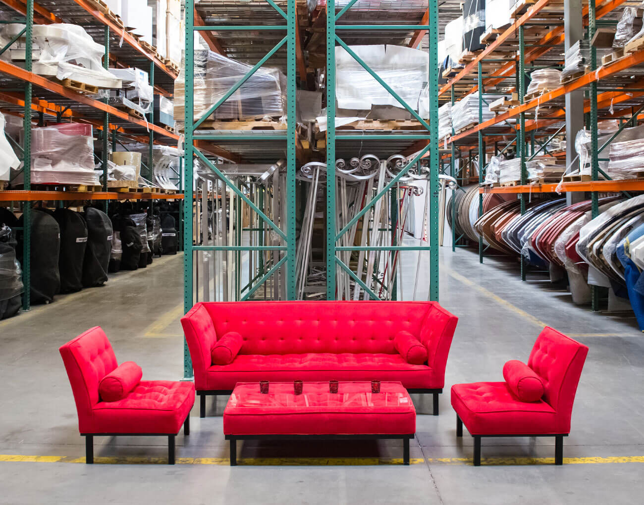 Plush red sofa and chairs arranged into a seating area in a warehouse.