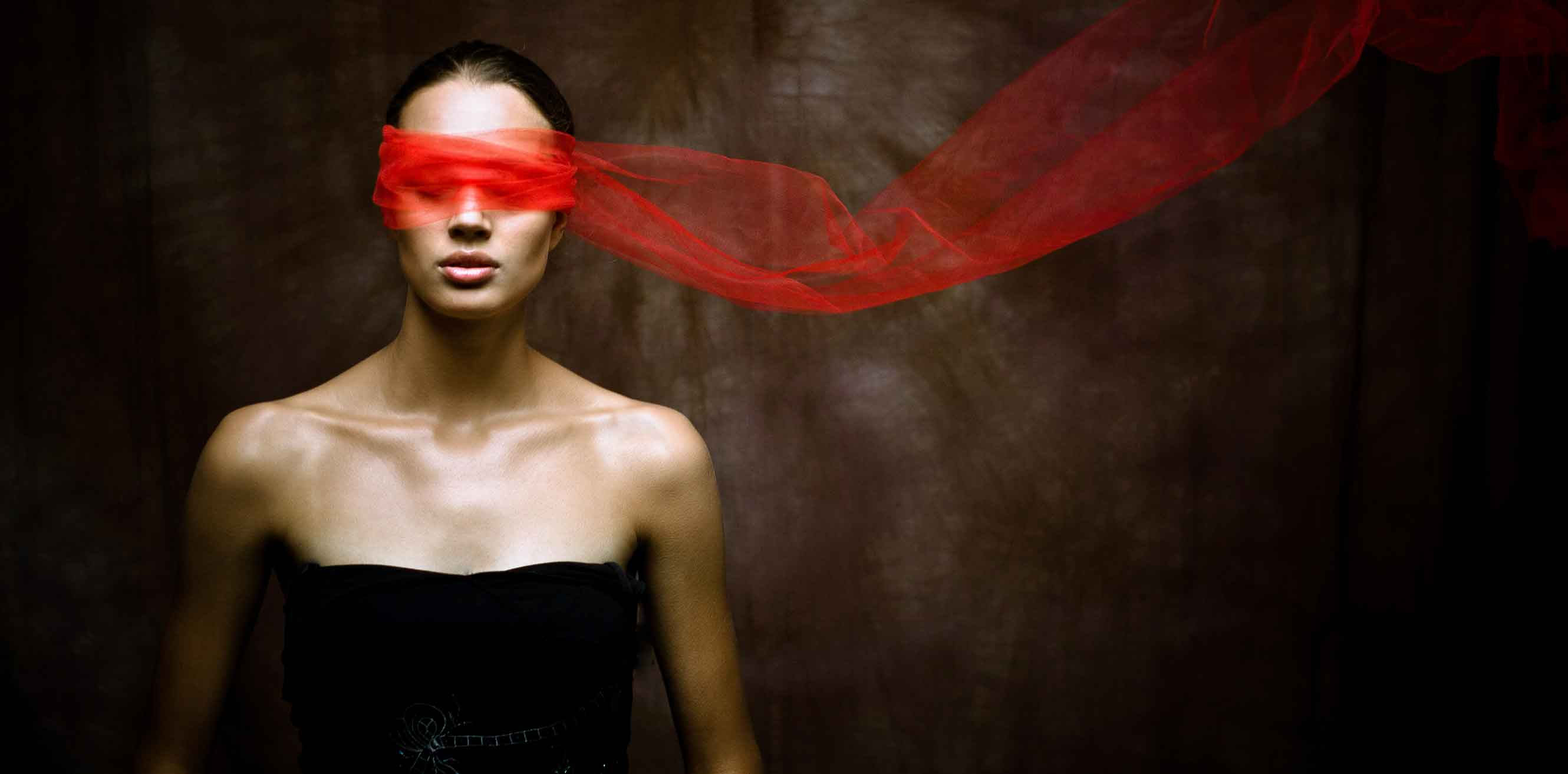 A woman wearing a blindfold of gauzy red fabric