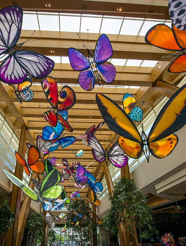 Oversized butterflies hang from the ceiling in an installation