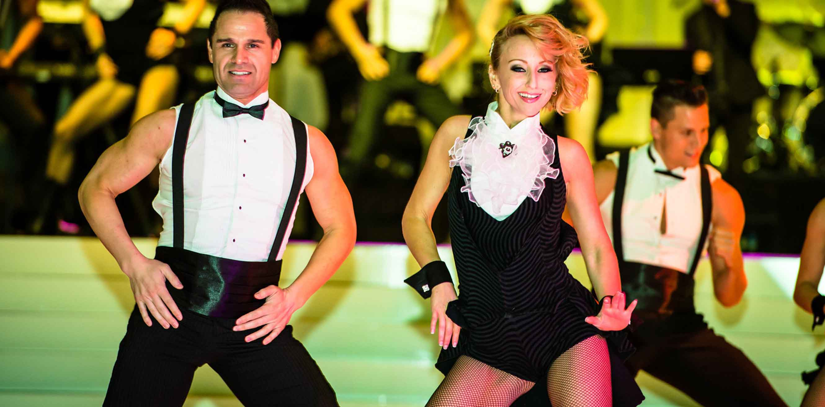 Close up of a pair of dancers in a tuxedo inspired costume