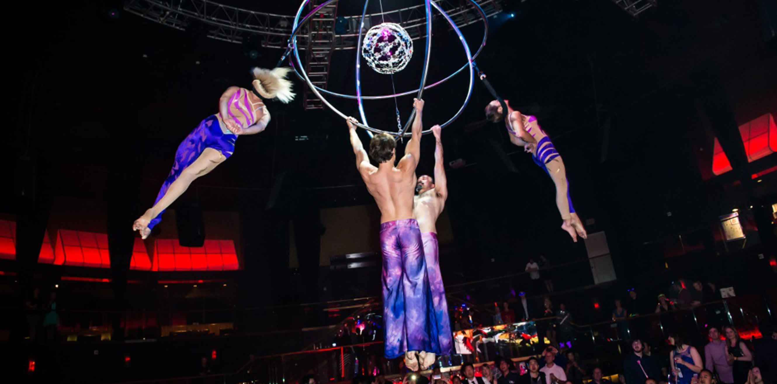 Acrobats hanging from a suspended sphere