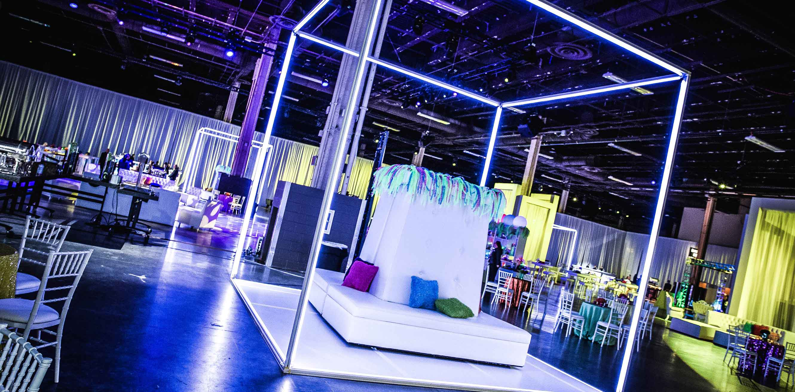 Neon box-like structure surrounding seating area in an event space
