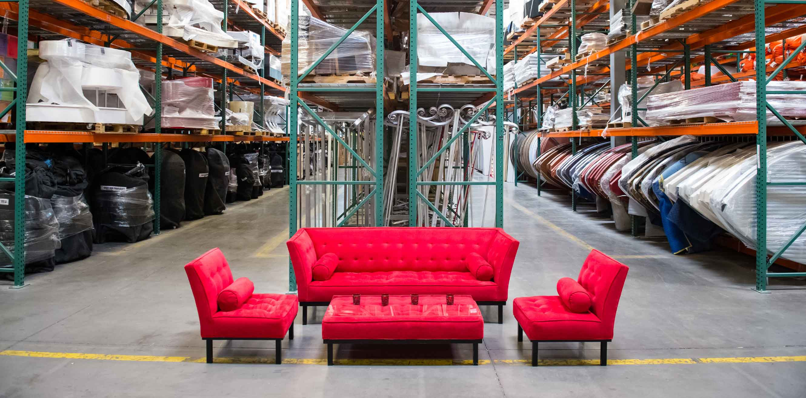 A red couch and chairs in a warehouse
