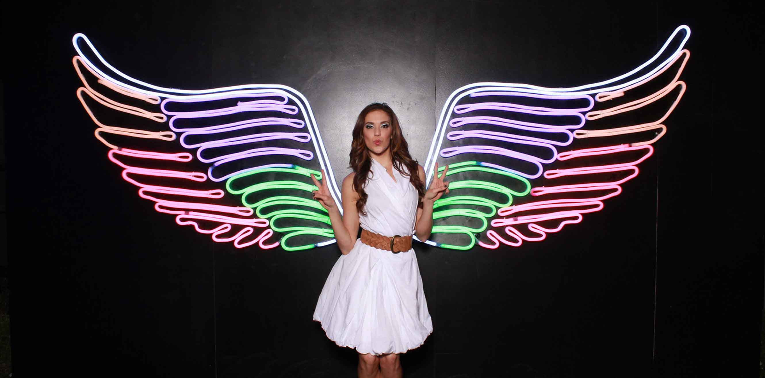 A woman posing in front of neon wings