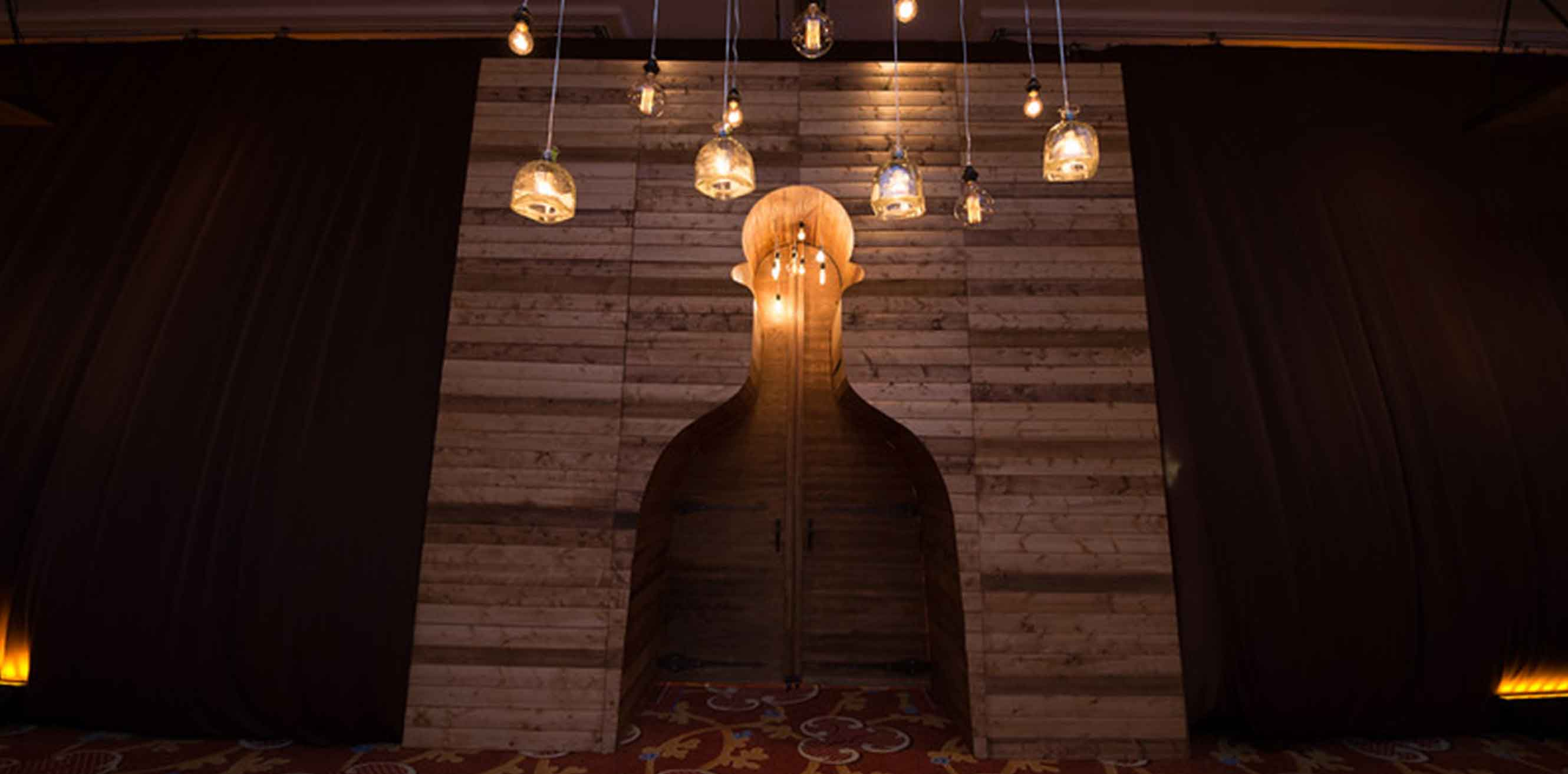 A wooden alcove with hanging Edison bulb lamps