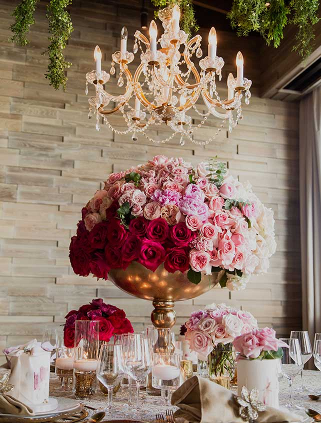 A large rose centerpiece under a chandelier