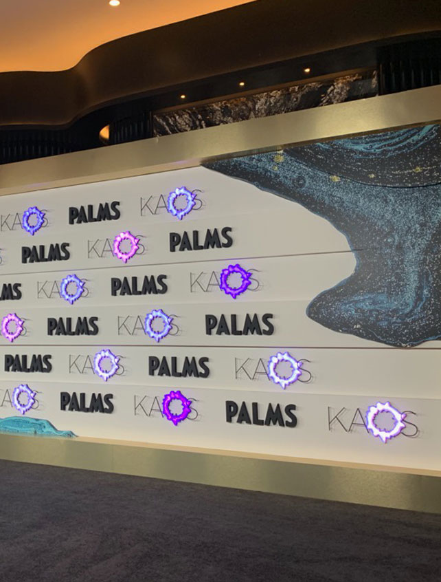 Palms and Kaos logos on a wall